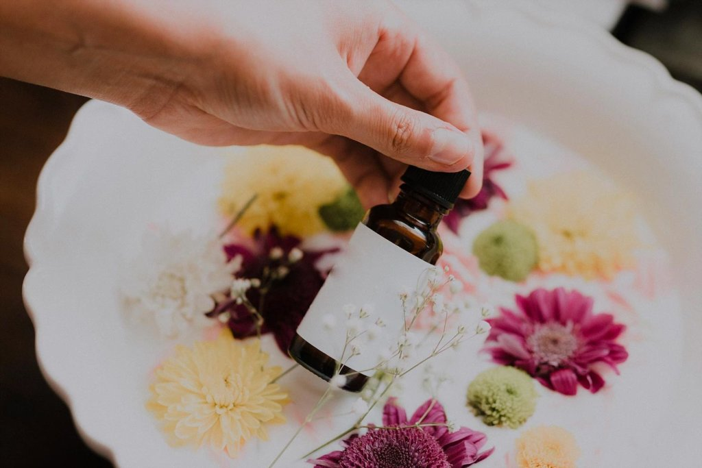 Woman's hand holding a glass cosmetic bottle over a basin filled with flowers