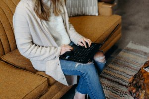 Blonde woman sitting on the couch with her laptop open