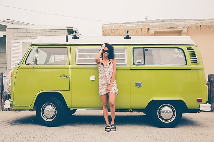 Young woman with curly hair and sunglasses standing in front of green VW van.