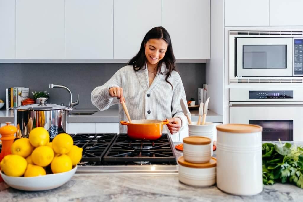 Young woman in white kitchen cooking a meal on the stovetop