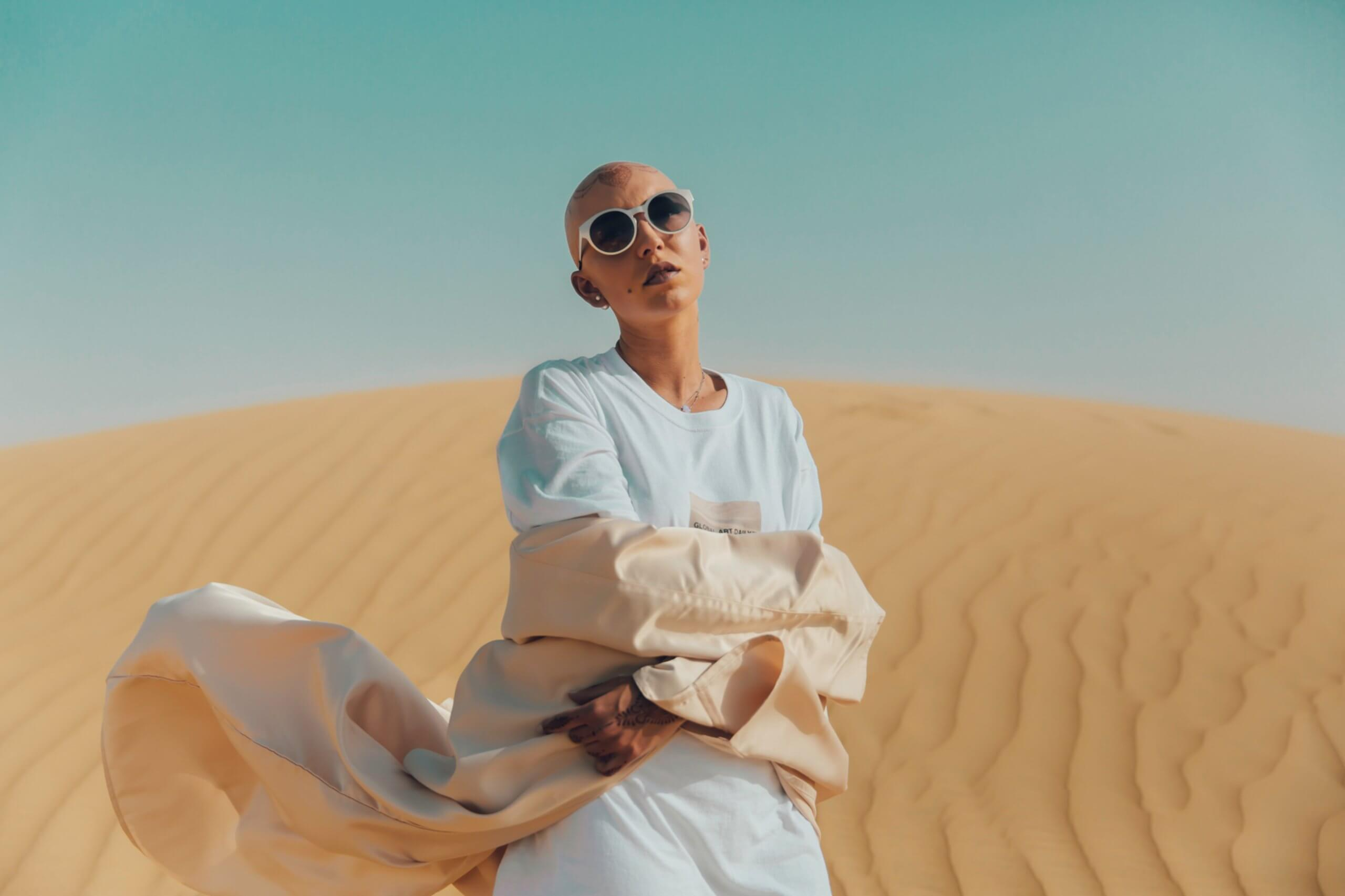 Bald woman with henna wearing flowing clothing in dessert