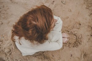 Aerial photo of a woman with auburn hair sitting on the sand