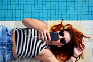 A young woman laying on her back, near a pool, looking at her cell phone with sunglasses on.