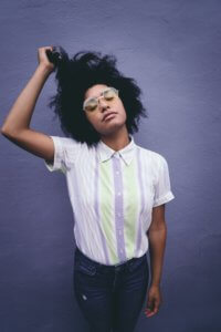 Young African American woman standing in front of a violet background, running her fingers through her hair.