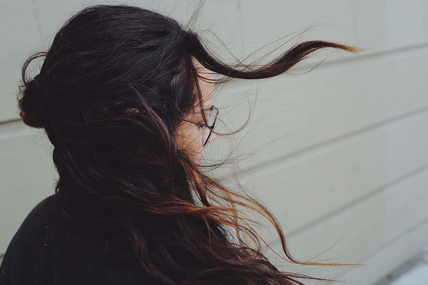 Woman wearing glasses with dark hair that is blowing in the wind.