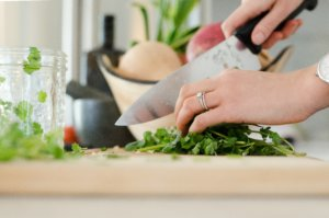 Woman's hand chopping vegetables and herbs