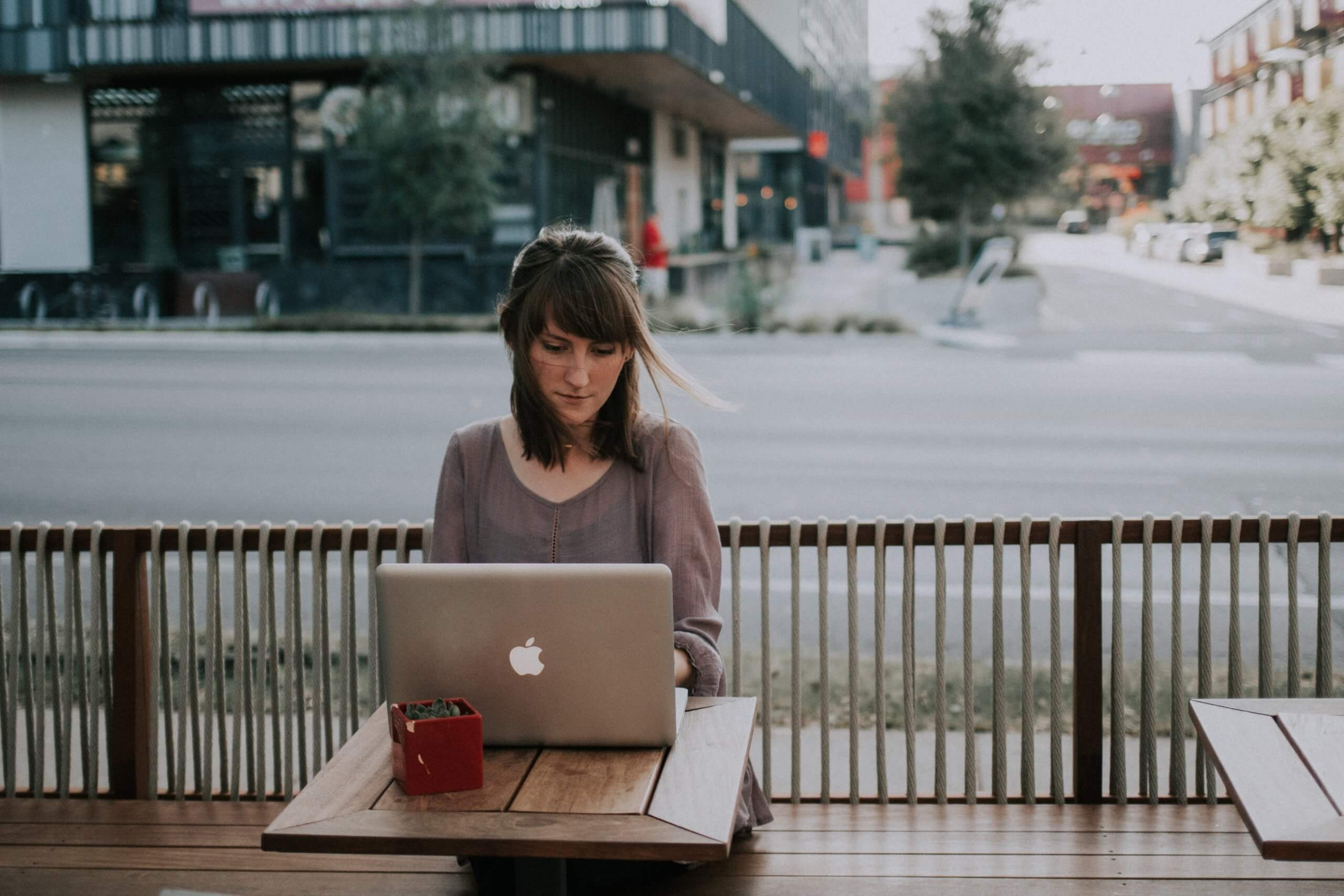 Brunette woman sitting at outdoor cafe, working at her laptop