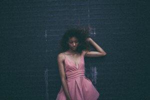 African-American women in pink dress, touching hair.