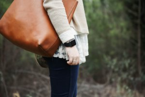 A woman wearing an Apple Watch carrying a brown leather tote bag.
