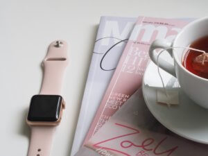 A cup of tea on a stack of magazines next to an Apple Watch